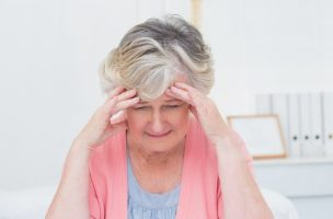 Tensed senior patient suffering from headache in clinic