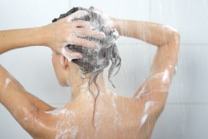 Woman washing head with shampoo