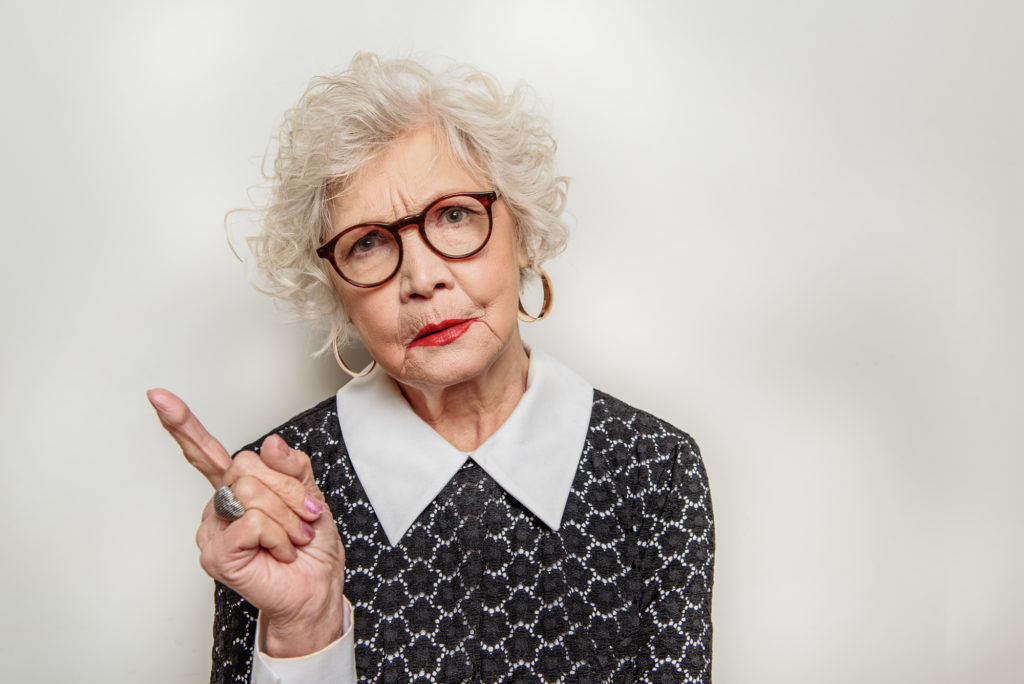 人差し指を立てる老婦人