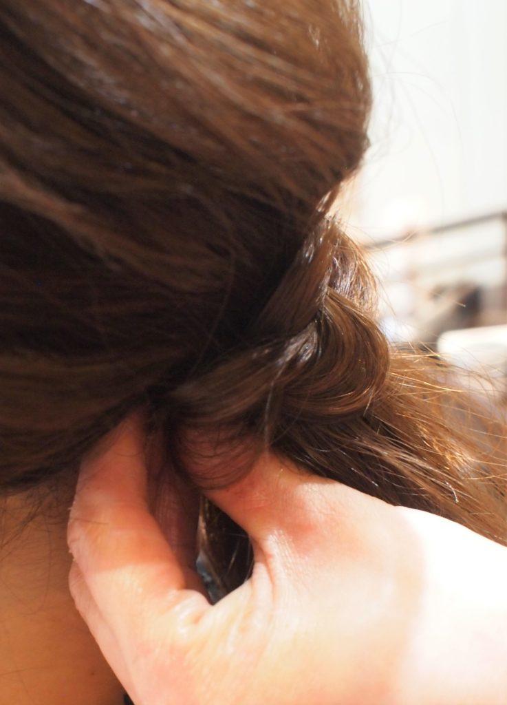 後ろの毛束に右の毛束を巻き付ける